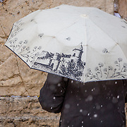 A man prays as snow and rain fall at The Western Wall on January 7, 2015 in Jerusalem, Israel. (Photo by Elan Kawesch)