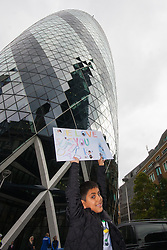 London, September 7th 2015. PICTURED: Young Joseph Demetriou with his poster supporting his Dad Jimmy, a tiny speck on the Face of the Gerkhin as he abseils down its gurved face. The Outward Bound Trust City Three Peaks Challenge in conjunction with The Royal Navy and Royal Marines Charity is a breathtaking abseiling endeavour on the greatest urban mountain range: The City of London.