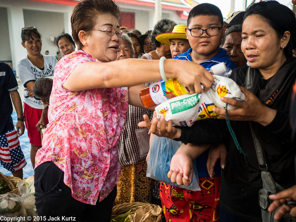 11 SEPTEMBER 2015 - BANGKOK, THAILAND: People receive rice and sandals during a food distribution for poor members of the community at Wat Kalayanamit in the Thonburi section of Bangkok. Food distribution is a common way of making merit in Chinese Buddhist temples. Wat Kalayanamit, a Thai Theravada temple, was founded by a Chinese-Thai family in the 1820s and observes both Thai and Chinese Buddhist traditions. The food distribution was not related to the temple's efforts to evict people living on the temple grounds, but many of the people at the food distribution live in the houses the temple plans to raze.    PHOTO BY JACK KURTZ
