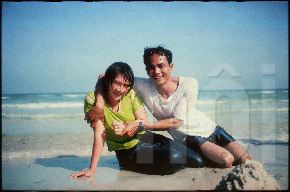 A Vietnamese couple sitting in the sand on Sao beach pose for the camera, Phu Quoc Island, Vietnam, Southeast Asia
