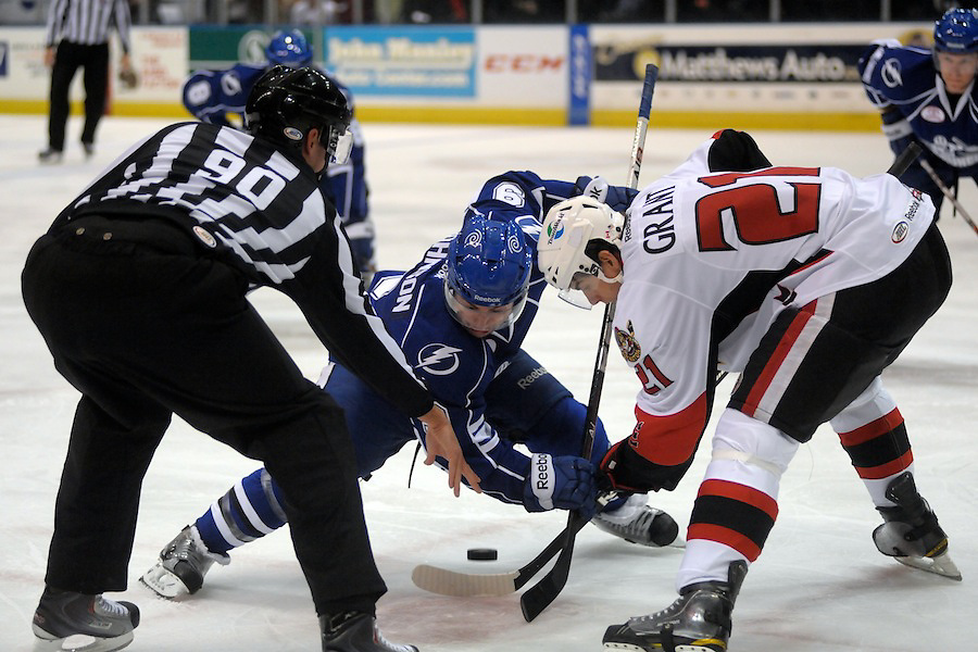 Syracuse Crunch center TYLER JOHNSON (9) and Binghamton Senators center DEREK GRANT (21) watch the puck drop during a first period face-off at the Broome County Veterans Memorial Arena in Binghamton, New York. Binghamton leads Syracuse 2-0 after the first period.