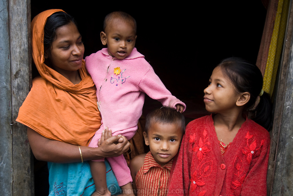 One of Shahnaz Hossain Begum's neighbors with her children in Bari Majlish village outside Dhaka, Bangladesh.  (Shahnaz Hossain Begum is featured in the book What I Eat: Around the World in 80 Diets.)   Shahnaz, a mother of four, got her first micro loan several years ago, from the Bangladesh Rehabilitation Assistance Committee (BRAC) to buy cows to produce milk for sale. She was able to earn enough to build several rental rooms next to her home. She and her family don't drink the milk that helps provide their income.