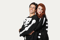 Portrait of couple in skeleton costume over gray background