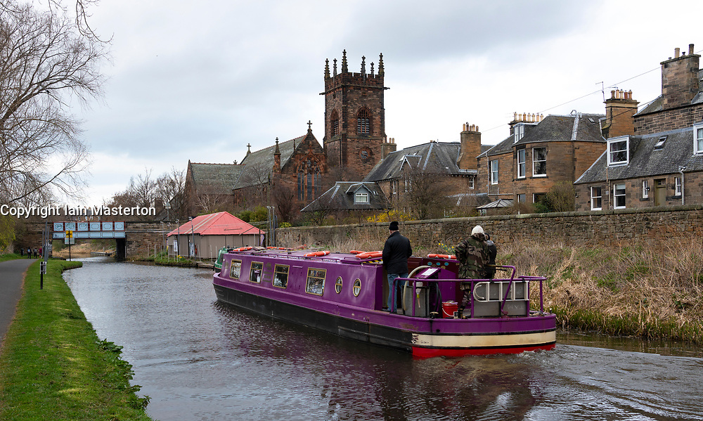 The Union Canal with narrowboat and Polwarth Parish church in early spring  in Edinburgh, Scotland, UK