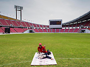 """A Red Shirt protester sits by herself in Rajamangala Stadium before a Red Shirt political rally. As many as 30,000 """"Red Shirts"""" are expected in Bangkok this week ahead of a Thai court ruling that could cause the collapse of the government of Yingluck Shinawatra, the Prime Minister. The Red Shirts are gathering in a suburban sports stadium before marching to the court. The Red Shirts are mostly farmers and rural Thais who support the Shinawatra government."""