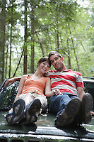 Couple sitting on car bonnet in forest portrait