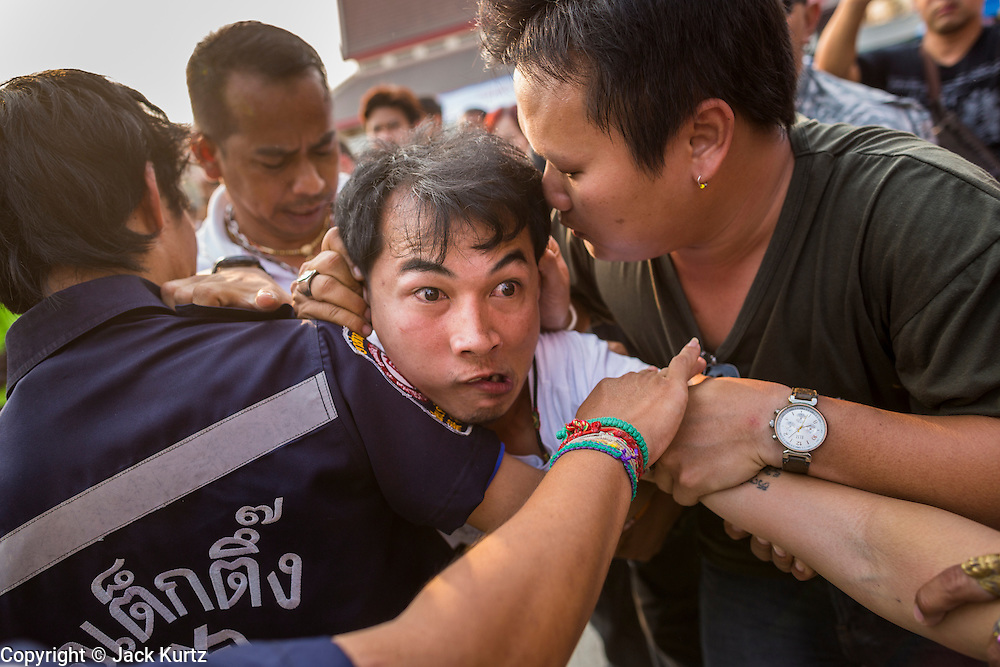 """15 MARCH 2014 - NAKHON CHAI SI, NAKHON PATHOM, THAILAND: Medics try to bring a man out of a trance state at the Wat Bang Phra tattoo festival. Wat Bang Phra is the best known """"Sak Yant"""" tattoo temple in Thailand. It's located in Nakhon Pathom province, about 40 miles from Bangkok. The tattoos are given with hollow stainless steel needles and are thought to possess magical powers of protection. The tattoos, which are given by Buddhist monks, are popular with soldiers, policeman and gangsters, people who generally live in harm's way. The tattoo must be activated to remain powerful and the annual Wai Khru Ceremony (tattoo festival) at the temple draws thousands of devotees who come to the temple to activate or renew the tattoos. People go into trance like states and then assume the personality of their tattoo, so people with tiger tattoos assume the personality of a tiger, people with monkey tattoos take on the personality of a monkey and so on. In recent years the tattoo festival has become popular with tourists who make the trip to Nakorn Pathom province to see a side of """"exotic"""" Thailand.   PHOTO BY JACK KURTZ"""