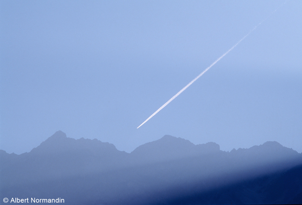 Rocky Mountains and Contrail as the sunrises, BC, Canada