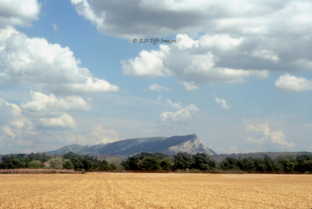 Landscape with a view of Mont Ste. Victoire across a wheat field near Aix en Provence.  Blue sky richly covered with white shapely clouds.