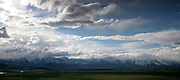Looking out over the valley at the Teton mountain Range with the expansive valley and clouds lit in patches of light