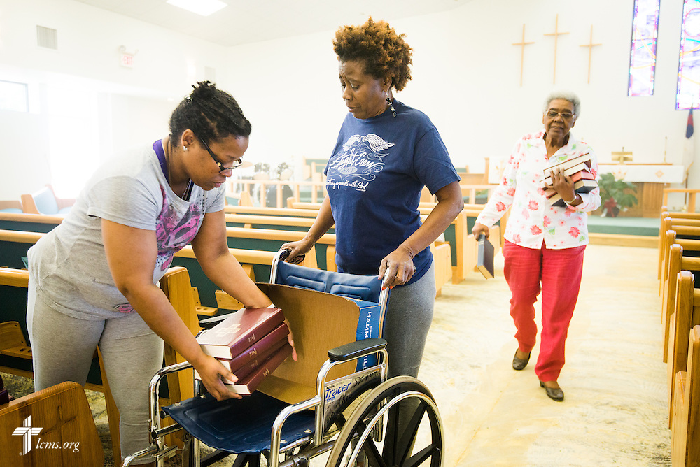 Nesiah Marshall (left) and Margaret Reed of St. Matthew Lutheran Church load books from the pew for transport out of the sanctuary on Saturday, May 3, 2014, in Pensacola, Fla., after floodwaters damaged the carpet and walls. LCMS Communications/Erik M. Lunsford