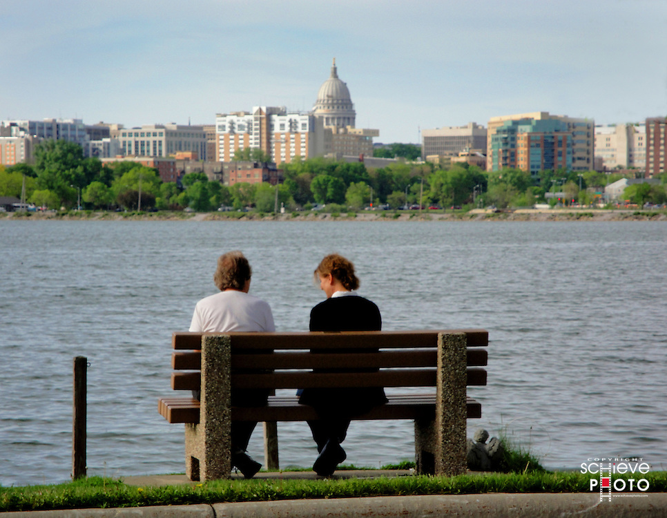 Two women on a bench overlooking the Madison, Wisconsin skyline.