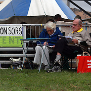 An elderly couple study form in the race guide during the Roxburgh Trotting Club Summer Festival Races, Roxburgh, Otago, New Zealand. 5th January 2012