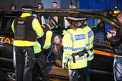 © Licensed to London News Pictures . 01/01/2016 . Manchester , UK . Police remove people from a cab following a row about the fare . Revellers in Manchester on a New Year night out at the clubs around the city centre's Printworks venue . Photo credit : Joel Goodman/LNP
