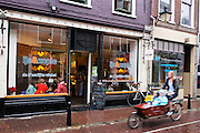 Een vrouw rijdt met een bakfiets met kinderen door de regen langs een ijswinkel in Utrecht.<br /> <br /> A woman passes in the rain on a cargo bike with children an ice cream store in Utrecht.