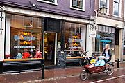 Een vrouw rijdt met een bakfiets met kinderen door de regen langs een ijswinkel in Utrecht.<br /> <br /> A woman passes in the rain on a cargo bike with children an ice cream store in Utrecht.
