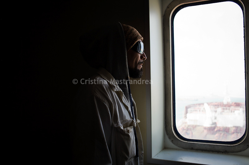 Trapani. Maurizio Sanacore guarda dall'oblo di una cabina. Maurizio operaio specializzato capo macchinista, occupa la petroliera del cantiere Navale di Trapani dopo essere stato licenziato insieme ai sui colleghi.