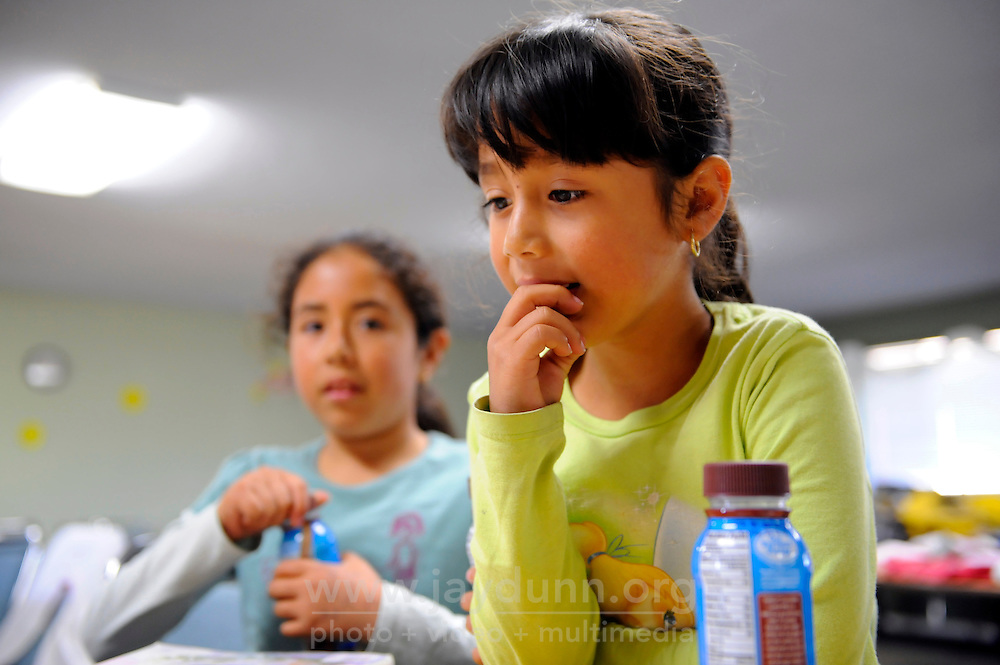 Children wait for their parents before a food distribution at the Vineyard Church, which runs a program in collaboration with the Food Bank of Monterey County.