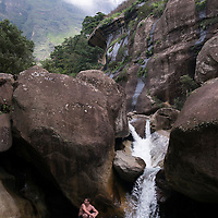 Refreshing water at the Tugela Gorge in the Northern Drakensberg area. Visit to the Northern Drakensberg Mountains. The iconic Amphitheatre rock formation is located in the Royal Natal National Park and is home to Tugela Falls (the second highest waterfall in the world). MODEL RELEASED.