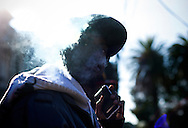 "Marquis ""B-eazi"" Johnson smokes a blunt outside his childhood home on Chase street in Lower Bottoms, West Oakland."