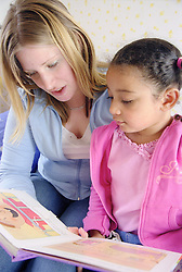 Single mother sitting on bed reading story book with young daughter,