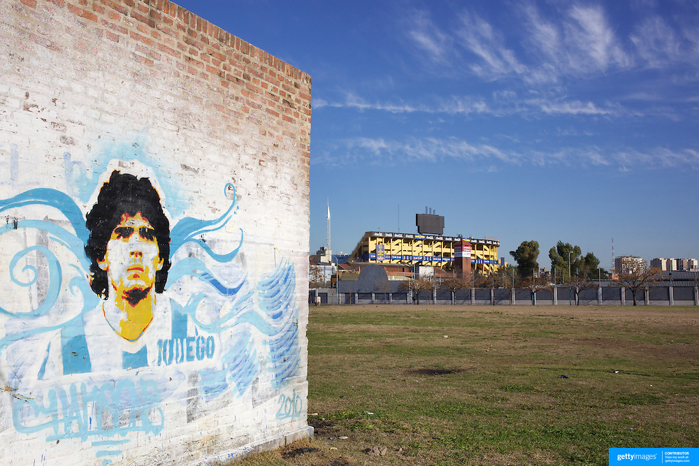 A mural of Argentina's most famous footballer, Diego Maradona, on a wall in La Boca region of Buenos Aires with the stadium of the regions famous football team, Boca Juniors, La Bombonera, in the distance. Buenos Aires, Argentina, 25th June 2010. Photo Tim Clayton..