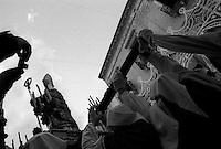 """""""Secondo la leggenda, [San Cataldo] sarebbe giunto a Taranto per volere divino: infatti si racconta che durante il soggiorno in Terra Santa, mentre era prostrato sul Santo Sepolcro, gli sarebbe apparso Ges? che gli avrebbe detto di andare a Taranto e di rievangelizzare la citt? ormai in mano al paganesimo. San Cataldo allora, salpando con una nave greca diretta in Italia, intraprese un lungo viaggio che lo portÚ a sbarcare nel porto dell'attuale Marina di San Cataldo, localit? a 11 km da Lecce che ha il suo nome. Sempre secondo la tradizione, il santo avrebbe lanciato un anello in mare per placare una tempesta, e in quel punto del Mar Grande si sarebbe formato un citro, cioË una sorgente d'acqua dolce chiamata """"Anello di San Cataldo""""..A Taranto Cataldo compÏ la sua opera evangelizzatrice, facendo abbattere i templi pagani e soccorrendo i bisognosi. In quel periodo egli si recÚ anche nei paesi limitrofi, tra cui Corato in provincia di Bari, di cui divenne patrono avendo per tradizione liberato la citt? dalla peste..MorÏ a Taranto l'8 marzo tra il 475 e il 480 e fu seppellito nella chiesa di San Giovanni in Galilea, allora duomo della citt?, e lÏ il suo corpo fu dimenticato per parecchi anni"""" (fonte Wikipedia http://it.wikipedia.org/wiki/San_Cataldo_vescovo)..La fotografia ha ad oggetto la c.d processione a terra che si svolge l'8 maggio: dopo la cerimonia d'u pregge (il privilegio), consistente nella consegna della Statua da parte delle Autorit? religiosa al Sindaco, il Santo viene trasportato su un'auto ricoperta di fiori e trasferito su una nave della Marina militare da dove ha inizio la successiva """"processione a mare""""."""