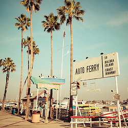 Newport Beach nostalgic vintage picture. The photo has a 1950s or 1960s vintage tone applied. Located in Newport Beach California, The Balboa Island Ferry has been operating since 1919 and carries people and cars from Balboa Peninsula to Balboa Island across Newport Harbor (Newport Bay). Also in the picture is the classic U Drive boat sign.