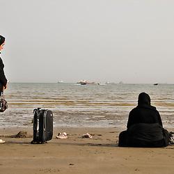 Women with luggage waiting on the beach. Bandar-e-Abbas, Iran