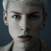 blonde boy with piercings looking directly at camera.