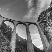 The Majestic Landwasser viaduct as seen from the Landwasser river, 65m (213 ft) below. Built between 1901 and 1902, the bridge is a signature element of the Rhaetian Railway line, blending timeless style with daily functionality as trains continue to thunder over it several times each day.
