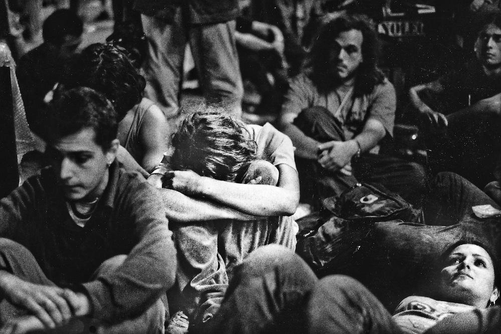 Genova, venerdì 20 luglio 2001. Giornata delle piazze tematiche.  Dopo il corteo della disobbedienza civile, allo stadio Carlini è il momento del pianto..Si apprende che la giornata ha avuto esiti tragici. Nella confusione dei primi momenti si parla di due morti e si cercano con preoccupazione i dispersi. In seguito le notizie saranno più chiare: in piazza Alimonda, nei pressi di via Tolemaide, è stato ucciso con un colpo di pistola un ragazzo di 23 anni, di Genova, Carlo Giuliani.