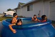 Children keep cool from the summer heat in the newly constructed Heritage Hills housing development in Macy, Nebraska.  From left to right, Christoper Guevara, 11, Ruby Guevara, 4, Alex Guevara, 8, and Sharee Jackson, 7...The 203rd Annual Harvest Celebration hosted by the Umonhon (Omaha) Tribe of Nebraska, held at the Wahnashe' Zhinga Park, in Macy, Nebraska from Aug. 2-5, 2007.  .Images taken for The Kellogg Foundation by Kainaz Amaria © 2007.