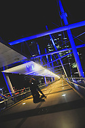 An unidentified person leaps into the air while crossing Brisbane's Kurilpa Bridge at night
