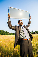 A young hip African American businessman holding a solar panel up to the sun. Green energy concept / Green business concept