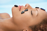 Woman receiving hot stone therapy head and shoulders close-up