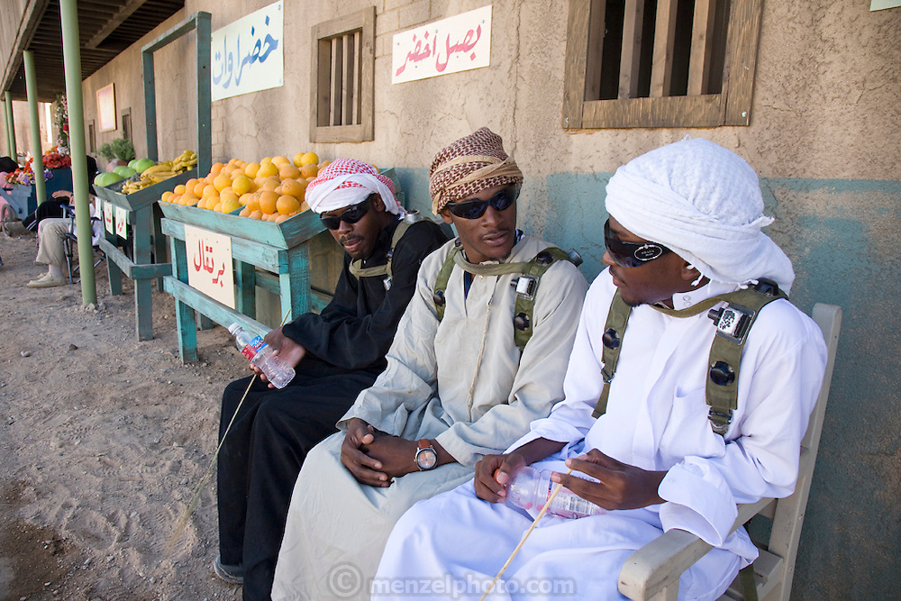 Actors dressed as Iraqi men sit at a market stall in the fabricated Iraqi village if Medina Wasl at Camp Irwin, California. The village is used for training soldiers deploying to Iraq.