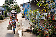A woman walks down the street at the village on Binh Thanh Island near Sadec, Vietnam.