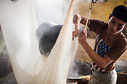 A factory worker drains soy milk from the paste using cheesecloth, Tofu factory, Malang, East Java.