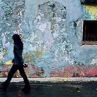 Woman walks in front of colorful wall, Yangshuo, Guilin, China
