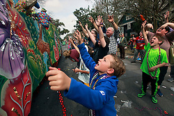 15 Feb 2015. New Orleans, Louisiana.<br /> Mardi Gras. Ben and friends catching beads at The Krewe of Thoth.<br /> Photo; Charlie Varley/varleypix.com