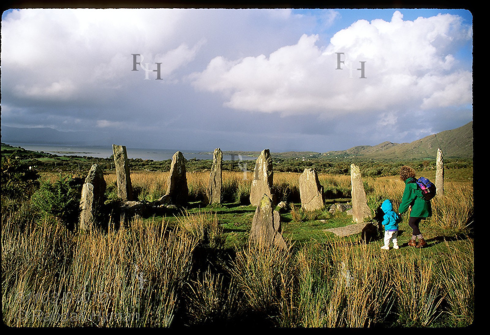 Mother and child explore 3000-year-old stone circle near Ardgroom once used as a calendar; Beara Peninsula, Ireland.