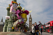 One week after the terrorist attack in the UK capital, Londoners and visitors to Britain look at the flower memorials left on Westminster Bridge (where pedestrians were mown down by a car)and outside the Palace of Westminster where armed police now guard the location where a police officer was killed, on 28th March 2017, London, England.