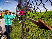 21 APRIL 2017 - CHANHASSEN, MN: A woman photographs flowers left on the fence in front of Paisley Park, the former home and recording studio of Prince. The superstar died from an accidental overdose of the opioid fentanyl on April 21, 2016. Friday was the first anniversary of his death. Crowds of people gathered at Paisley Park, which is now a museum, to honor the Minnesota born musician.     PHOTO BY JACK KURTZ