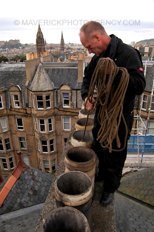 Feature on Chimney Sweeps. Pictured Kirk McLenaghan (short hair) and Bert Boat from Auld Reekie chimney sweeps cleaning chimneys on the roof of a block of flats in Viewforth Edinburgh.