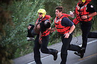 10/25/2000-Rescue workers rush a young boy to a waiting ambulance after he was pulled from the Los Angeles river near Anaheim street on Wednesday, Oct. 25. Two boys fell in the river. Both boys were pronounced dead.