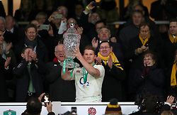 England's Dylan Hartley celebrates with the Autumn International trophy during the Autumn International match at Twickenham Stadium, London.