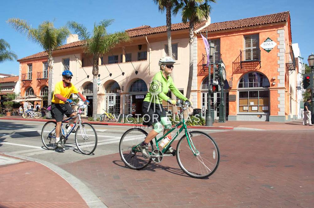Couple riding a bicycle on State street. Santa Barbara, California. USA.
