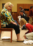 A young girl washes the feet of an adult during a Holy Thursday Mass. (Sam Lucero photo)