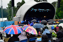 © Licensed to London News Pictures. 24/08/2013. London, UK The Royal Choral Society together with the Royal Philharmonic Concert Orchestra, performs an evening of the choral classics in Heavy rain at Live by the Lake. The English Heritage concert season returns to Kenwood House in Hampstead, London, with  Live by the Lake. The season includes Suede, a Choral Greats concert, Keane, an outdoor live screening of Singin' in the Rain featuring the Royal Philharmonic Concert Orchestra, Opera Alfresco and an evening of Gershwin. . Photo credit : Stephen Simpson/LNP